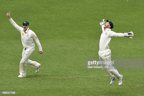 Steve Smith and Peter Nevill of Australia celebrate victory during day five of the First Test match between Australia and New Zealand at The Gabba on...