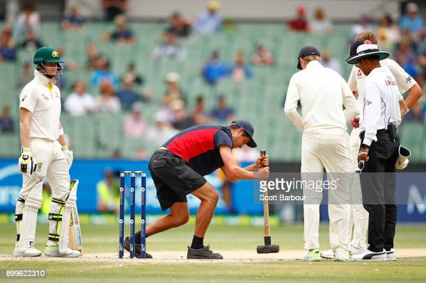 Steve Smith of Australia and bowler Stuart Broad of England look on as the groundsman tries to flatten the bowlers foot marks on the pitch during day...