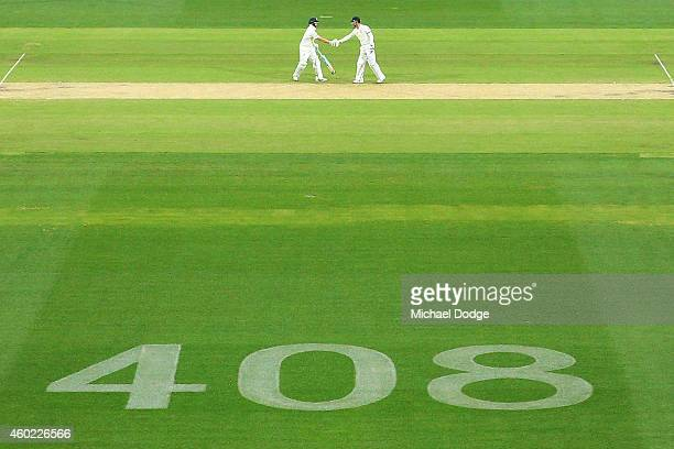 Steve Smith of Australia and Michael Clarke shake hands after reaching their 100 run partnership with the number 408 displayed as a tribute to the...