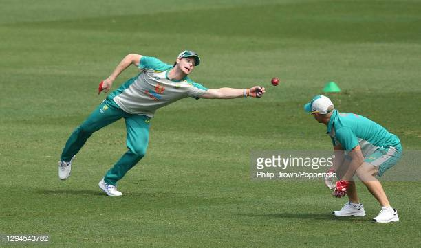Steve Smith of Australia dives for a catch watched by David Warner during an Australian training session before the third Test match against India at...
