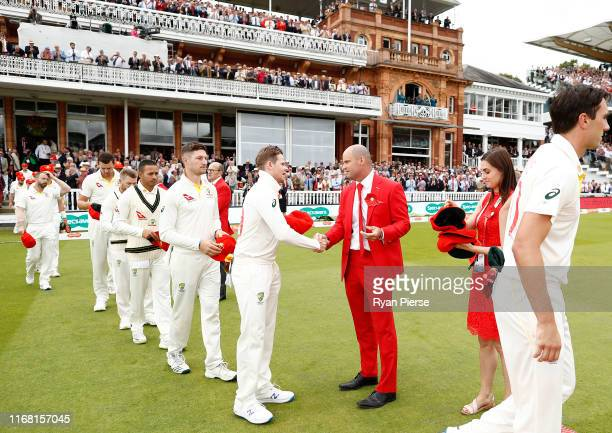 Steve Smith of Australia presents his red cap to Andrew Strauss on Ruth Strauss Day during day two of the 2nd Specsavers Ashes Test between England...