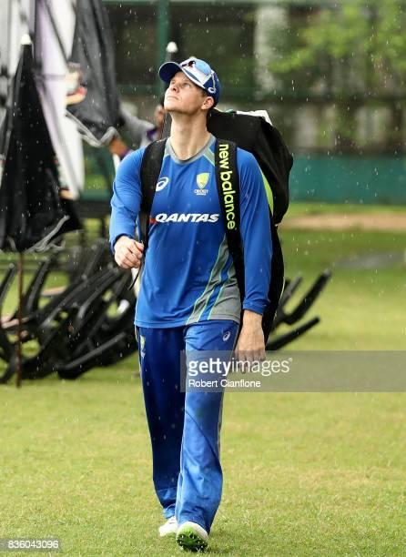 Steve Smith of Australia walks off the ground as rain falls during an Australian Test team nets session at SherE Bangla National Cricket Stadium on...