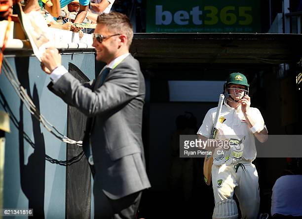 Steve Smith of Australia walks out to bat as former Australian Captain Michael Clarke signs autographs during day four of the First Test match...