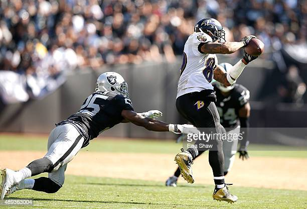 Steve Smith of the Baltimore Ravens completes a pass in front of D.J. Hayden of the Oakland Raiders in the third quarter at Oakland-Alameda County...