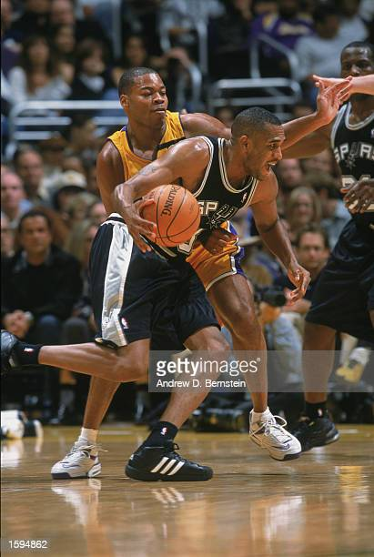 Steve Smith of the San Antonio Spurs drives past Devean George of the Los Angeles Lakers during the NBA game at Staples Center on October 29 2002 in...
