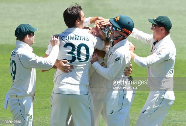 Steve Smith, Pat Cummins ,Travis Head and Marnus Labuschagne of Australia hug Cameron Green of Australia after he caught Virat Kohli of India during...