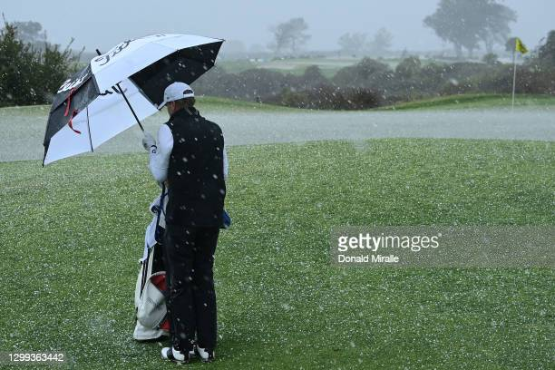 Steve Stricker and his caddie stand on the 17th hole in a hailstorm during round two of the Farmers Insurance Open at Torrey Pines on January 29,...