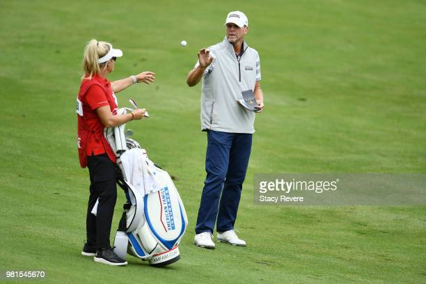 Steve Stricker catches his ball from his caddie and wife Nicki Stricker in the 18th fairway during the first round of the American Family Insurance...