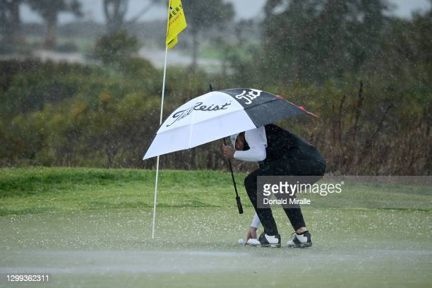 Steve Stricker picks up his ball from the 17th hole green in a hailstorm during round two of the Farmers Insurance Open at Torrey Pines on January...