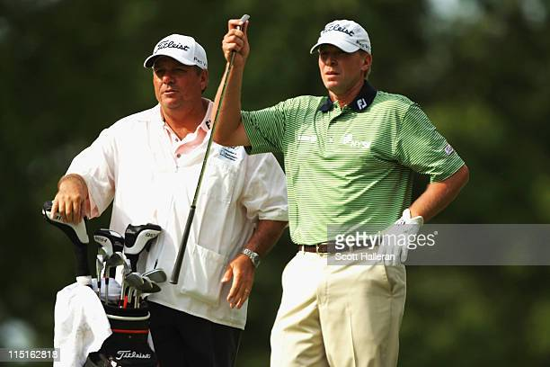 Steve Stricker pulls a club on the ninth hole as his caddie Jimmy Johnson looks on during the second round of the Memorial Tournament presented by...
