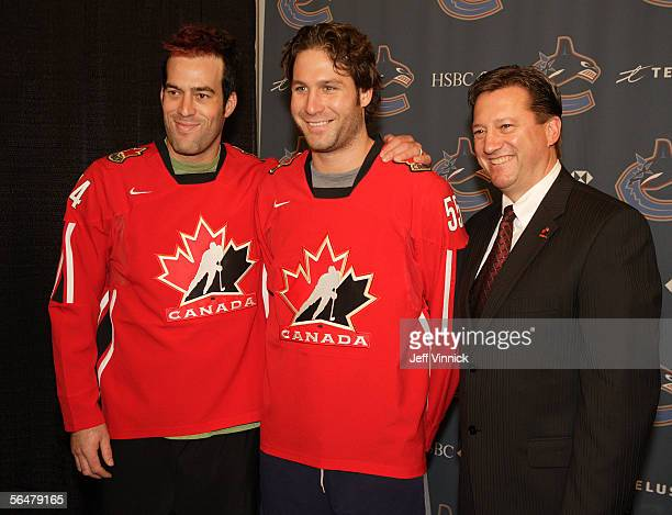 Steve Tambellini , Director of Player Personnel with Hockey Canada, looks on as Ed Jovanovski and Todd Bertuzzi show off their Team Canada Olympic...