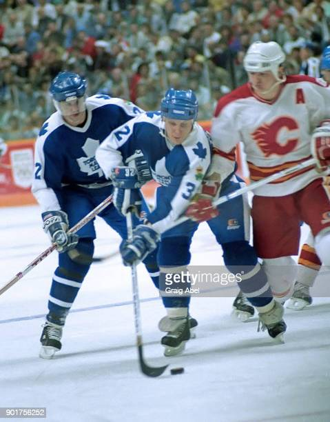 Steve Thomas and Rick Vaive of the Toronto Maple Leafs skate against Al MacInnis of the Calgary Flames during NHL game action on February 20 1987 at...