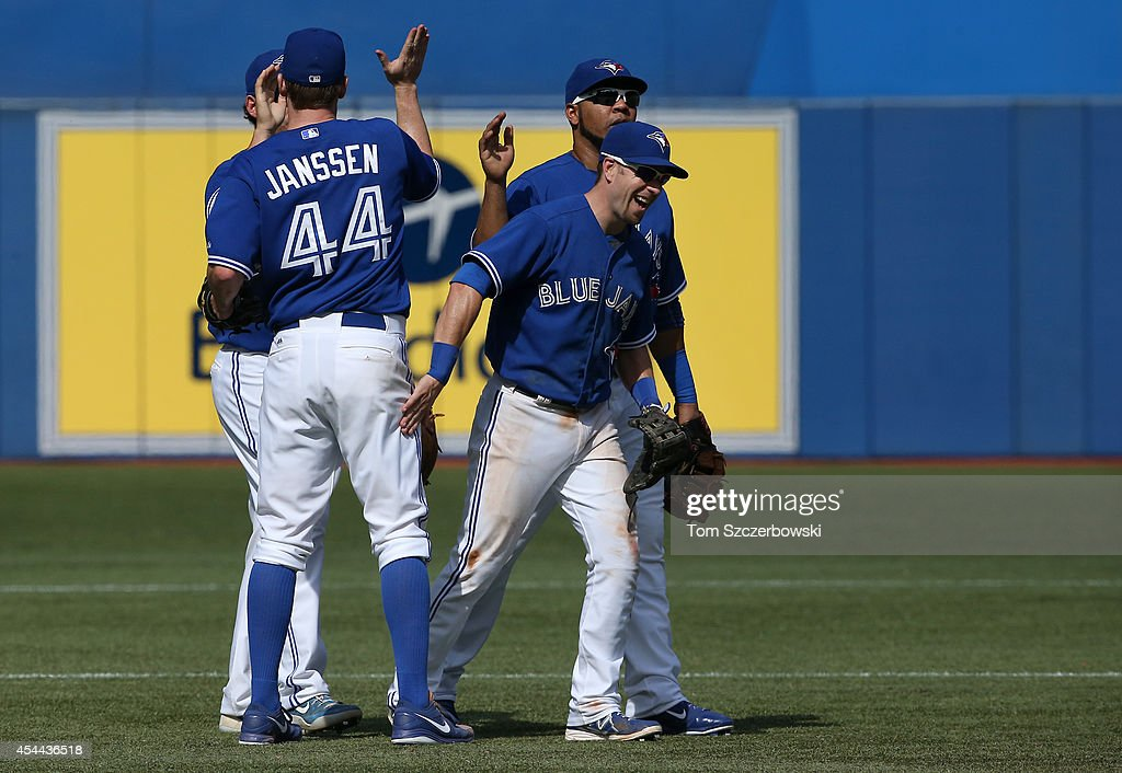 Steve Tolleson #18 of the Toronto Blue Jays celebrates their victory with Edwin Encarnacion #10 during MLB game action against the New York Yankees on August 31, 2014 at Rogers Centre in Toronto, Ontario, Canada.