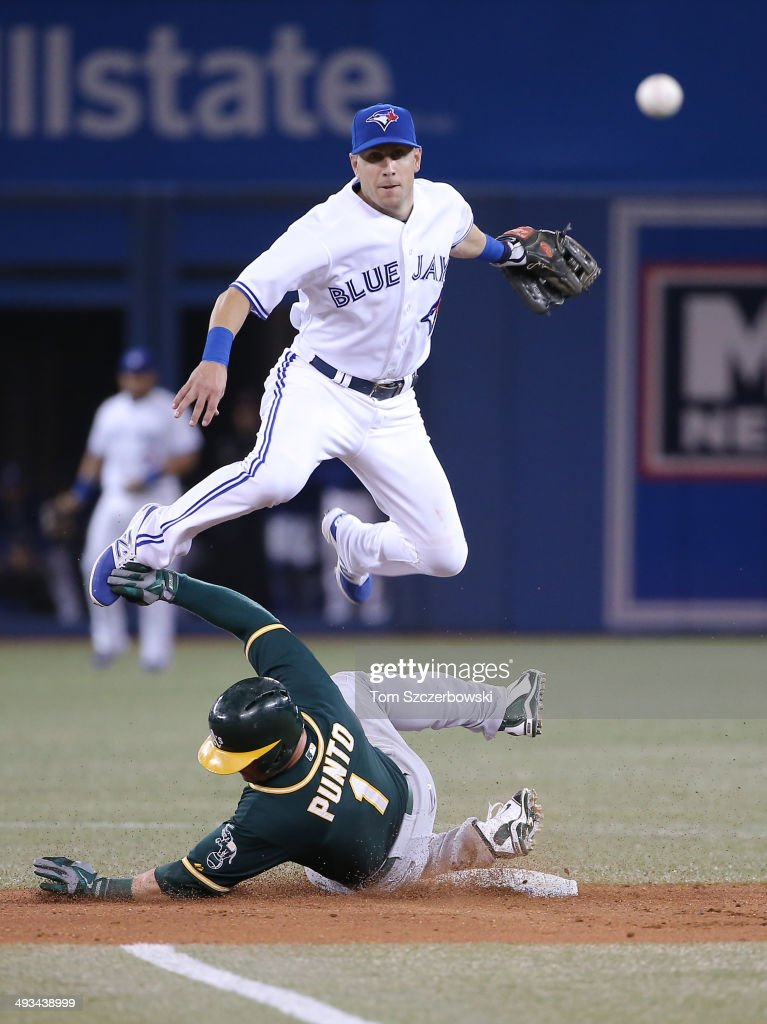 Steve Tolleson #18 of the Toronto Blue Jays turns a double play in the seventh inning during MLB game action as Nick Punto #1 of the Oakland Athletics slides into second base on May 23, 2014 at Rogers Centre in Toronto, Ontario, Canada.