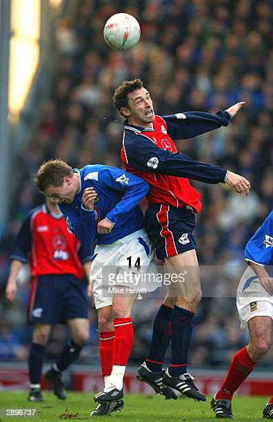 Steve Torpey of Scunthorpe gets above Matthew Taylor of Portsmouth during the FA Cup Fourth Round match between Portsmouth and Scunthorpe United at...