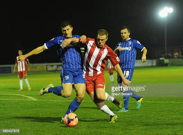 Steve Towers of Brackley Town is tackled by John Mousinho of Gillingham during the FA Cup First Round Replay match between Brackley Town and...