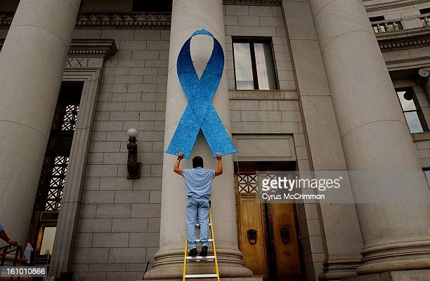 Steve Vargas an electrician lifts one of two blue ribbons that are being displayed on the columns on the east side of the City and County Building to...