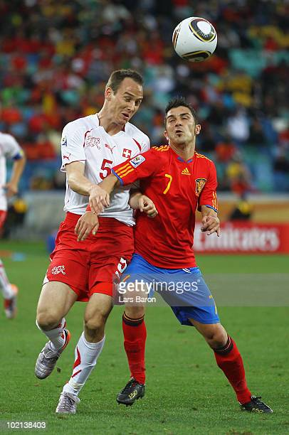 Steve von Bergen of Switzerland and David Villa of Spain compete for the ball during the 2010 FIFA World Cup South Africa Group H match between Spain...