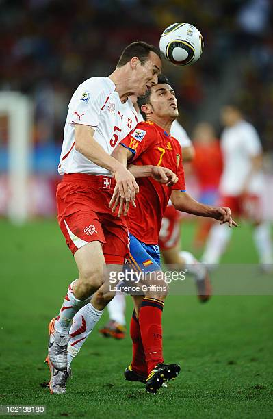 Steve von Bergen of Switzerland and David Villa of Spain jump for the ball during the 2010 FIFA World Cup South Africa Group H match between Spain...