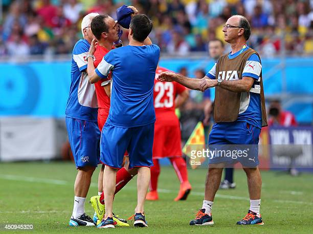 Steve von Bergen of Switzerland is assisted off the pitch after a collision during the 2014 FIFA World Cup Brazil Group E match between Switzerland...