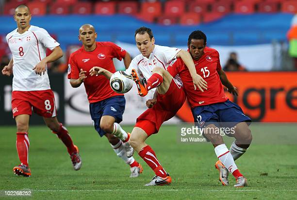 Steve von Bergen of Switzerland is tackled by Humberto Suazo and Jean Beausejour of Chile during the 2010 FIFA World Cup South Africa Group H match...