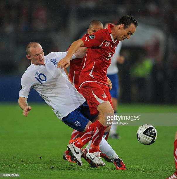Steve von Bergen of Switzerland is tackled by Wayne Rooney of England during the EURO 2012 Group G Qualifier between Switzerland and England at St...