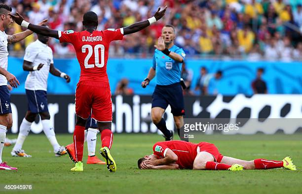 Steve von Bergen of Switzerland lies on the pitch after a collision during the 2014 FIFA World Cup Brazil Group E match between Switzerland and...