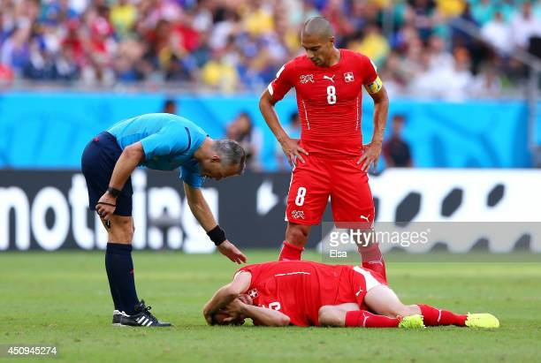 Steve von Bergen of Switzerland lies on the pitch as referee Bjorn Kuipers stands over during the 2014 FIFA World Cup Brazil Group E match between...