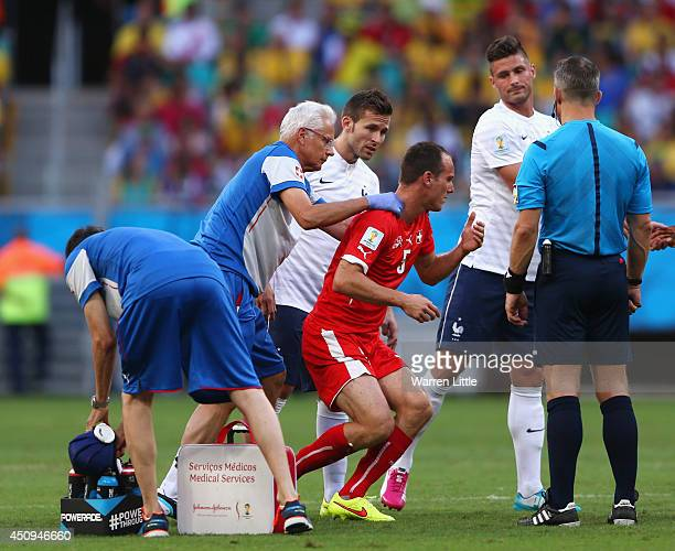 Steve von Bergen of Switzerland receives treatment after a collision with Olivier Giroud of France during the 2014 FIFA World Cup Brazil Group E...