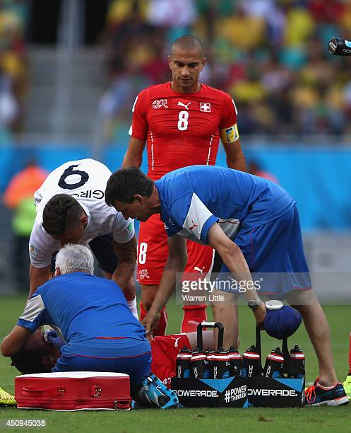 Steve von Bergen of Switzerland receives treatment as teammate Gokhan Inler and Olivier Giroud of France look on during the 2014 FIFA World Cup...