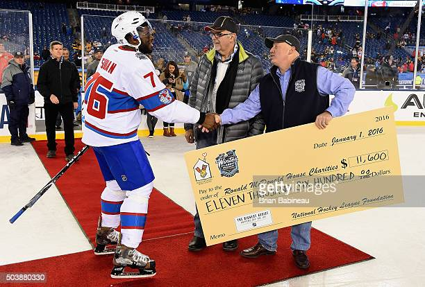 Steve Wallach President of the Boston CoOp for McDonald's and NHL Deputy Commissioner Bill Daly present a check to PK Subban of the Montreal...