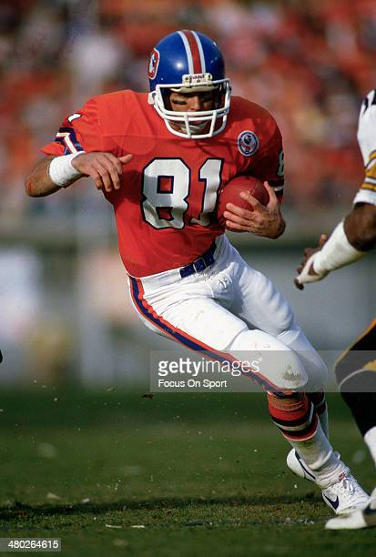 Steve Watson of the Denver Broncos carries the ball against the Pittsburgh Steelers during an NFL football game circa 1983 at Mile High Stadium in...