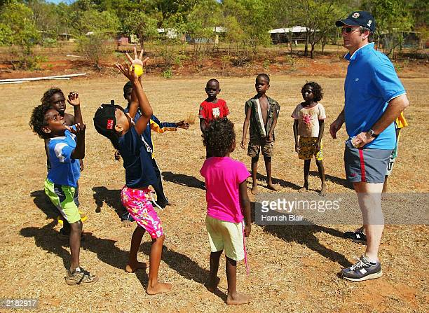 Steve Waugh of Australia teaches the locals to catch a cricket ball on July 22 2003 during a team visit to an Aboriginal settlement on Melville...