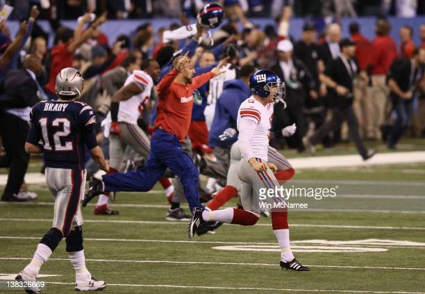 Steve Weatherford of the New York Giants runs past Tom Brady as he celebrates after defeating the New England Patriots 21-17 to win Super Bowl XLVI...