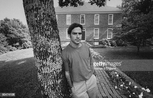 Steve Wilson the son of murder victim opthalmologist Dr Jack Wilson sadly leaning against tree in front of twostory brick house where his dad was...