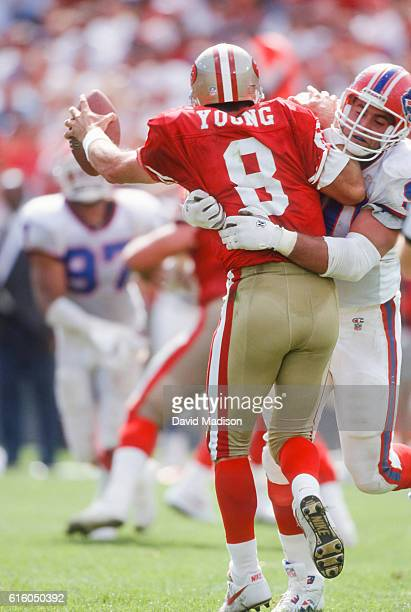 Steve Young of the San Francisco 49ers is hit by Ray Agnew of the Buffalo Bills during a National Football League game between San Francisco and...