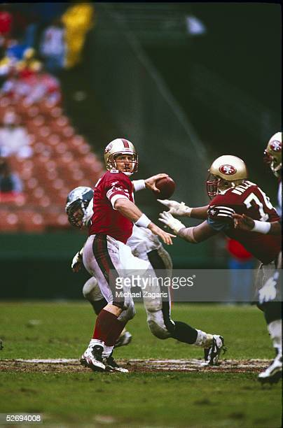 Steve Young of the San Francisco 49ers looks to pass against the Philadelphia Eagles during the 1996 NFC Wild Card Playoff at 3Com Park at...