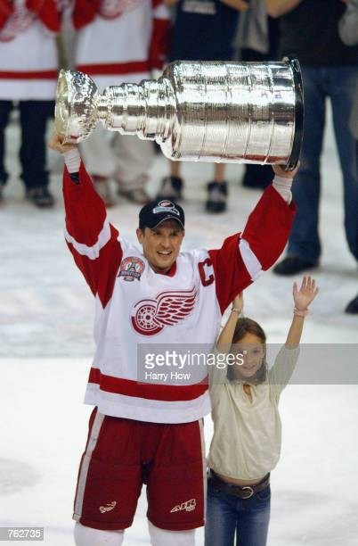 Steve Yzerman of the Detroit Red Wings hoists the Stanley Cup next to his daughter Isabella after defeating the Carolina Hurricanes 31 in game five...