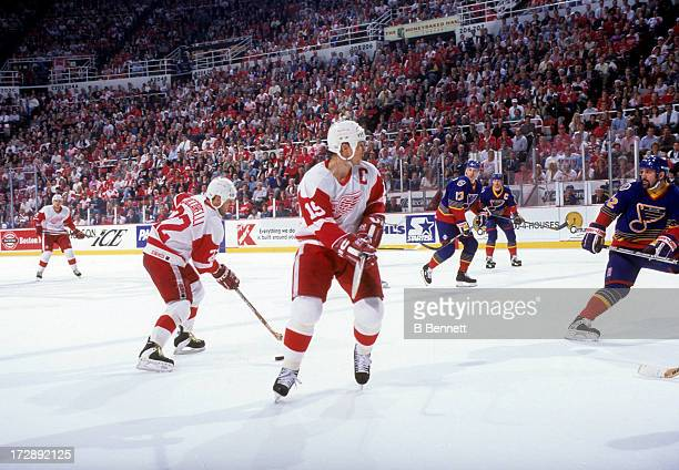 Steve Yzerman of the Detroit Red Wings skates on the ice as teammate Dino Ciccarelli skates with the puck during Game 7 of the 1996 Conference...