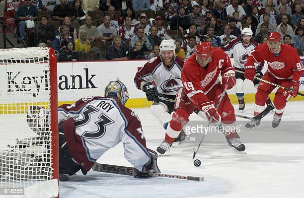 Steve Yzerman of the Detroit Red Wings tries to slip one past Patrick Roy of the Colorado Avalanche in the first period during game six of the...