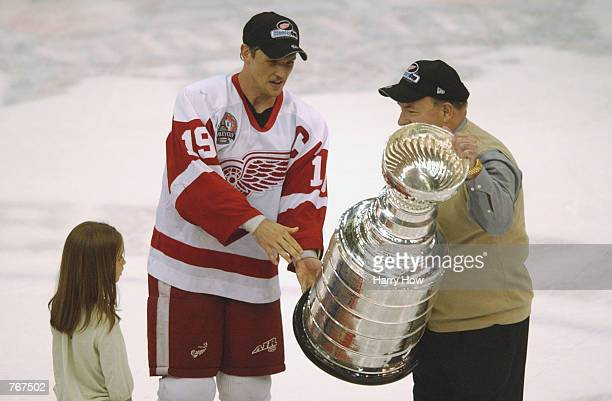 Steve Yzerman of the Detroit Red Wings with daughter Isabella by his side hand the Stanley Cup over to Head Coach Scotty Bowman after defeating the...