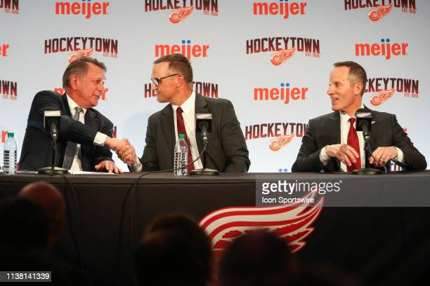 Steve Yzerman shakes hands with Ken Holland while Detroit Red Wings Governor President and CEO Christopher Illitch looks on during a press conference...