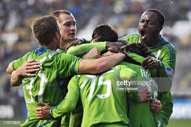 Steve Zakuani and his teammates of Seattle Sounders FC jump onto Alvaro Fernandez after he scored the tying goal during the game against the...
