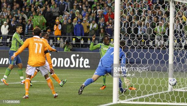 Steve Zakuani of the Seattle Sounders FC scores a goal against goalkeeper Tally Hall of the Houston Dynamo at Qwest Field on March 25 2011 in Seattle...