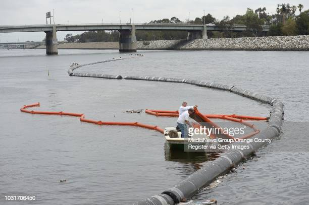 Steve Zieg, back, and Ron Blackledge, of Frey Environmental, ready the trash boom at the mouth of the Los Angeles River in Long Beach on Wednesday....