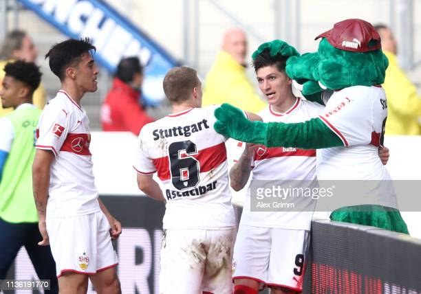 Steve Zuber of VfB Stuttgart celebrates after scoring his team's first goal with the mascot Fritzle and Santiago Ascacibar of VfB Stuttgart during...