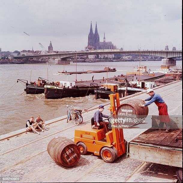 Stevedores move barrels with a forklift on a wharf on the Rhine River in Cologne The double spired Cologne cathedral is in the background Ca 19501980