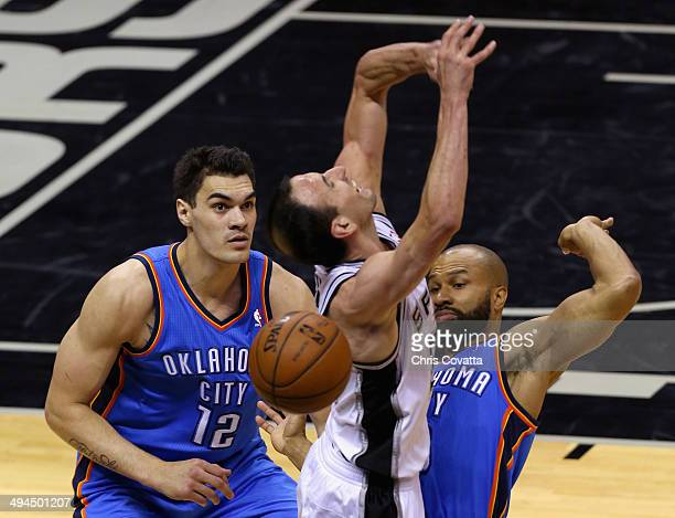 Steven Adams and Derek Fisher of the Oklahoma City Thunder defend Manu Ginobili of the San Antonio Spurs in the first half during Game Five of the...