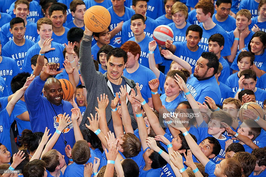 Steven Adams of Oklahoma City Thunder and basketball coach Kenny McFadden pose with children during the New Zealand Basketball Academy Launch at ASB Sports Centre on August 17, 2014 in Wellington, New Zealand.