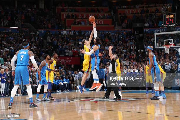 Steven Adams of the Oklahoma City Thunder and Zaza Pachulia of the Golden State Warriors reach for the opening tipoff during the game on April 3 2018...